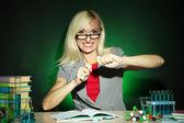 恶人的化学老师坐在桌旁,在黑暗的彩色背景 — 图库照片