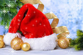 Composition with Santa Claus red hat and Christmas decorations on light background — Stockfoto