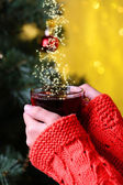 Hands holding mug of hot drink, close-up, on Christmas tree background — Foto Stock