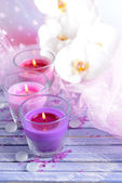 Beautiful colorful candles and orchid flowers, on color wooden table, on light background — Zdjęcie stockowe