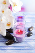 Beautiful colorful candles, spa stones and orchid flower,on color wooden table, on light background — Stok fotoğraf