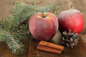 Red frosted apples with fir branch and bumps on wooden background — Photo
