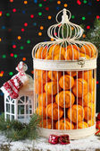 Tangerines in decorative cage with Christmas decor, on shiny background — Stockfoto