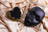 Decorative black heart and mask, on color fabric — Stock Photo