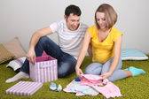 Young pregnant woman with her husband folding baby wear on floor at home — Stock Photo