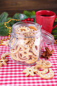 Delicious Christmas cookies in jar on table on wooden background — Photo