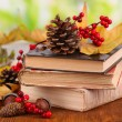 Books and autumn leaves on wooden table on natural background — Stock Photo #37515817