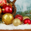 Christmas decorations in basket with snow on table on bright background — Stock Photo #37518897