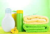 Baby cosmetics and towels on wooden table, on green background — Stock Photo