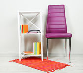 Beautiful interior with modern color chair, books on wooden stand, on wall background — Stock Photo