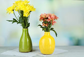Beautiful flowers in vases, on wooden table, on light background — Stock Photo
