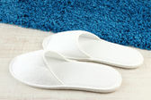 White slippers on floor background — Stock Photo