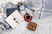 Composition with warm plaid, book, cup of hot drink on color carpet background — Stock Photo