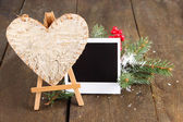 Decorative heart on easel and empty photo paper, on wooden background — Foto Stock