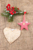 Decorative heart and star on rope, on burlap background — Zdjęcie stockowe
