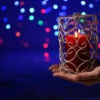Candle in hand on blur lights background — Stock Photo