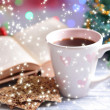 Composition of book with cup of coffee and Christmas decorations on table on bright background — Photo #37524505