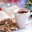 Composition of book with cup of coffee and Christmas decorations on table on bright background — Stok fotoğraf #37524505
