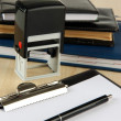 Stock Photo: Stamp with notepads and clipboard on table