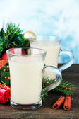 Cups of eggnog with fir branches and Christmas decorations on table on bright background — Stockfoto