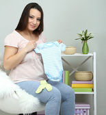 Young pregnant woman sitting on armchair and folding baby wear on wall background — Stok fotoğraf