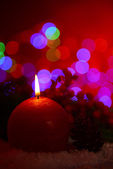 Candle and Christmas tree bud on wooden table on bright background background — Stock Photo