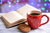 Composition of book with cup of coffee on table on bright background — Stok fotoğraf