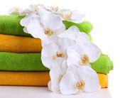 Colorful towels and orchid flowers, isolated on white — Stock Photo