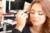 Mladý kluk kadeřník dělá make-up krásná žena v salonu krásy — Stock fotografie