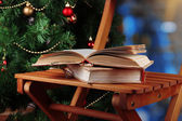 Composition with books on chair on Christmas tree background — Stock Photo