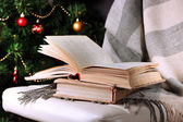 Composition with books and plaid on chair on Christmas tree background — Stock Photo