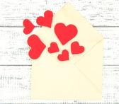 Lindo velho envelope com corações decorativos em fundo de madeira — Foto Stock