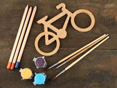 Decorative bicycle with drawing set on wooden background — 图库照片