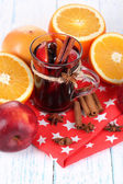 Fragrant mulled wine in glass on napkin and wooden table close-up — Stock Photo