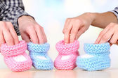 Hands with crocheted booties for baby, on light background — 图库照片