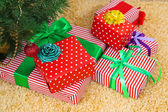 Many colorful presents with luxury ribbons on color carpet background — Stockfoto