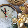 Clock with fir branches and Christmas decorations under snow close up — Stock Photo #37556731