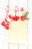 Blank sheet with Christmas decor hanging on white wooden wall — Stockfoto
