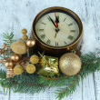 Clock with fir branches and Christmas decorations on wooden background — Stock Photo #37599069