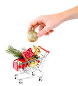 Hand and Christmas gifts in shopping trolley, isolated on white — Stockfoto