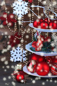 Christmas decorations on dessert stand, on wooden background — Stockfoto