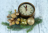 Clock with fir branches and Christmas decorations on wooden background — Stock fotografie