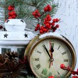 Clock with fir branches and Christmas decorations on table on wooden background — Stock Photo #37611081