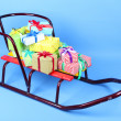 Sledge with Christmas presents, on blue background — Stock Photo #37611165