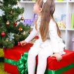 Little girl setting on big present box near Christmas tree in room — Stock Photo #37613187
