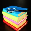 Stock Photo: Color books with magnifying glass on table on black background