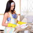 Beautiful young womwashing dishes in kitchen — Stock Photo #37617619