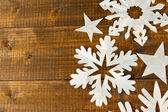 Beautiful paper snowflakes on wooden background — Stock Photo