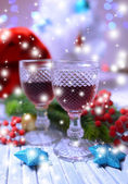 Wine glasses and Christmas decorations on bright background — Stock Photo