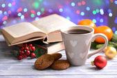 本书带杯咖啡和圣诞装饰品上明亮的背景表格的组成 — 图库照片